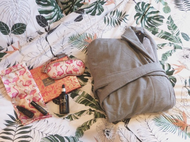 flatlay featuring a grey dressing gown, a pink flamingo eye mask and bag, a bottle of bath oil, eye oil and a facial oil sitting on top of the bed linen which has a plant theme