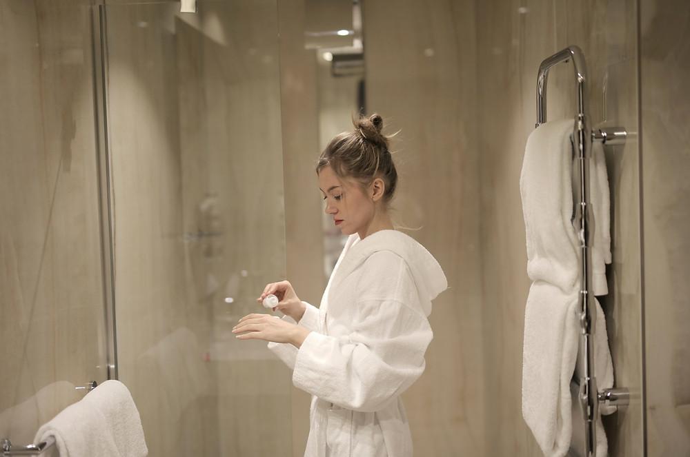 woman in a white bathrobe inside a bathroom putting cream on her hands