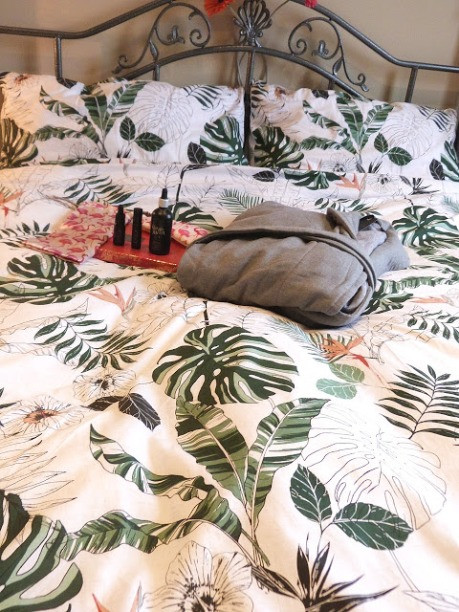 photo shows a grey dressing gown on the bed linen which has a plants on it.