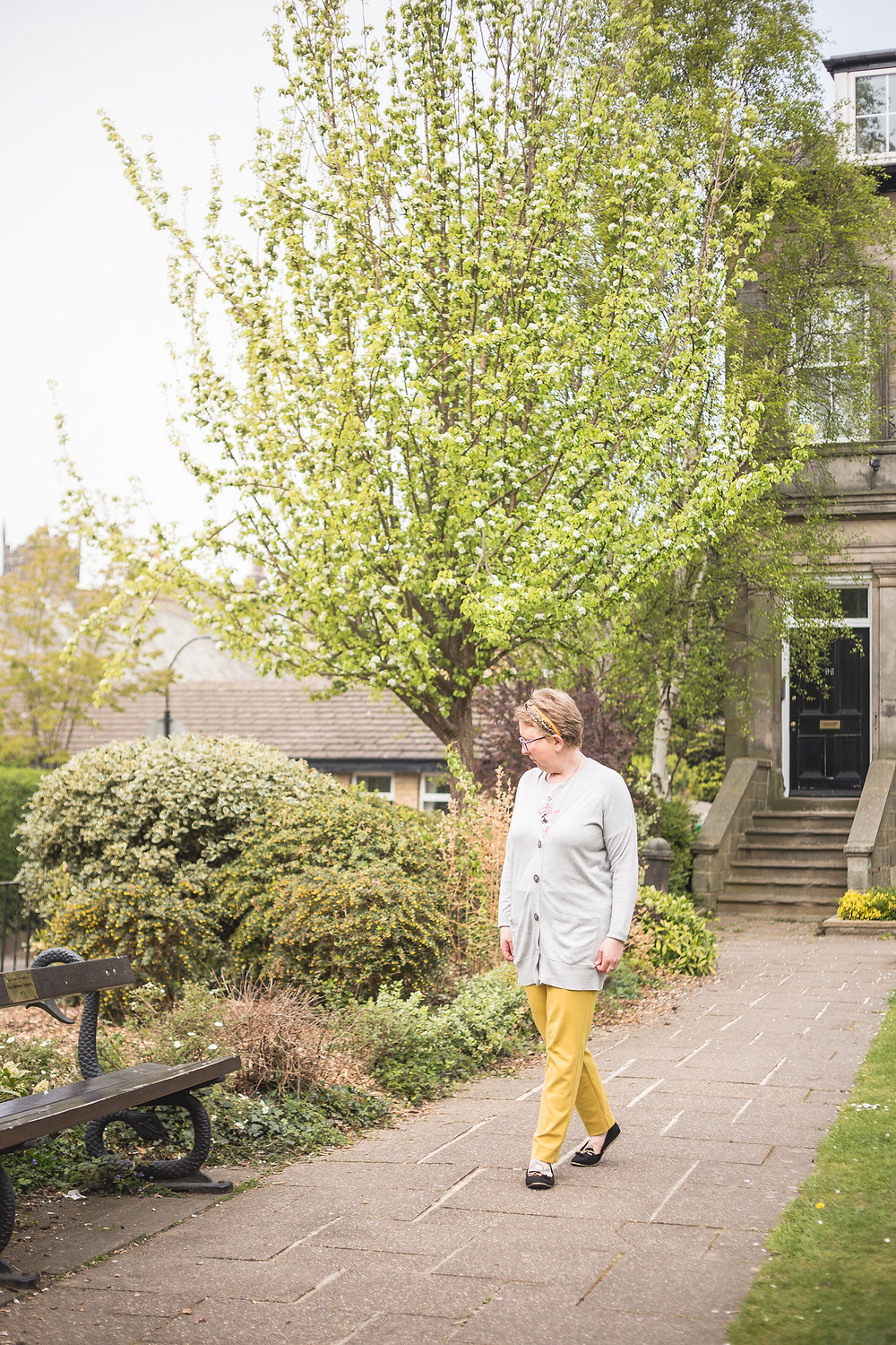 Sarah walking wearing yellow trousers and a grey cardigan over the top of a thin grey jumper she is wearing black shoes. You can see trees, bushes, plants and a front door to a flat. There is also a bench just in shot.