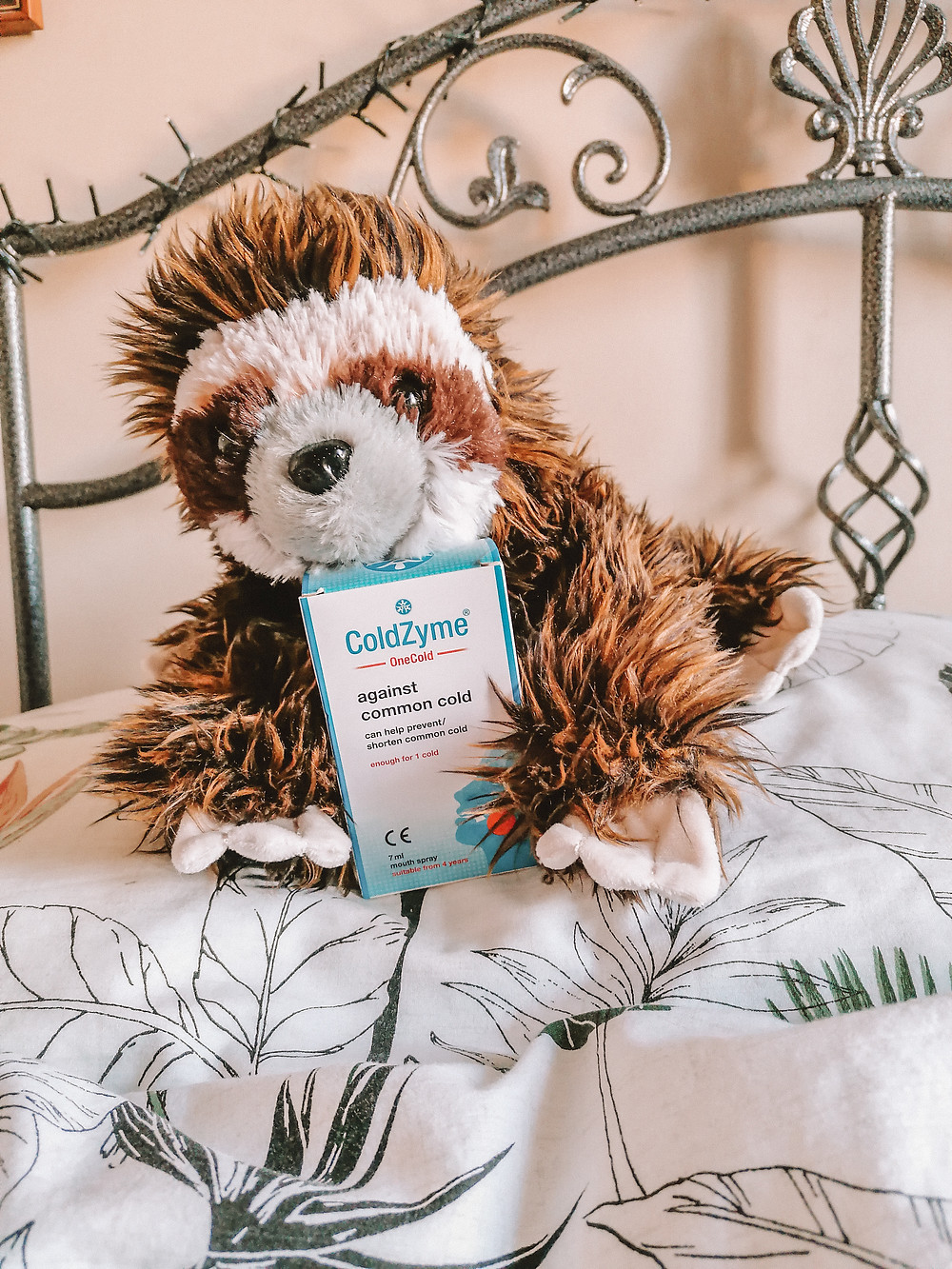 A stuffed toy sloth on a bed holding a box of ColdZyme cold spray