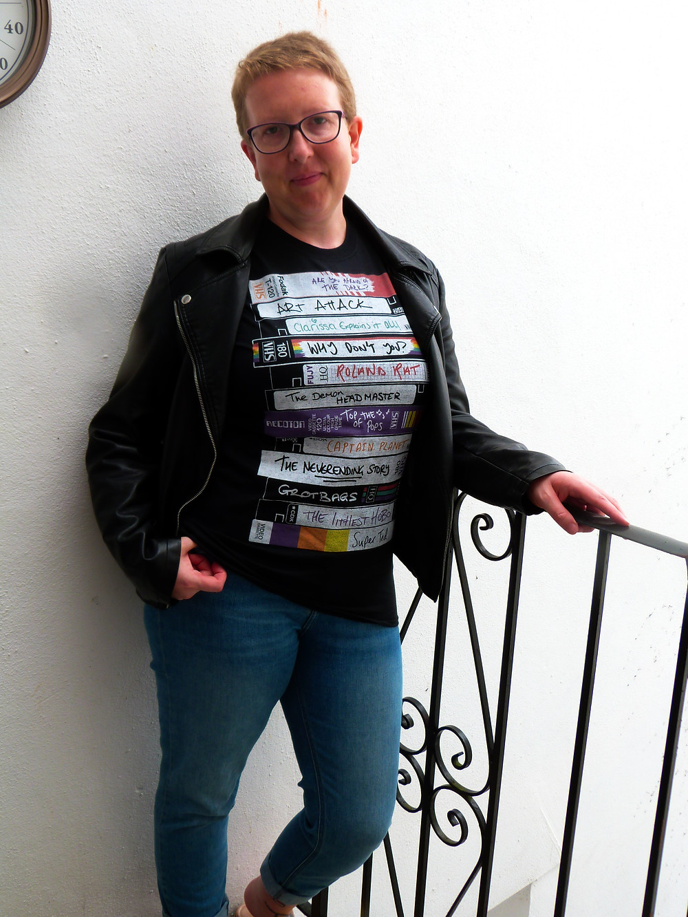 Sarah standing against a white wall wearing a black t shirt with vhs tapes on the front with names of old tv shows on and blue jeans