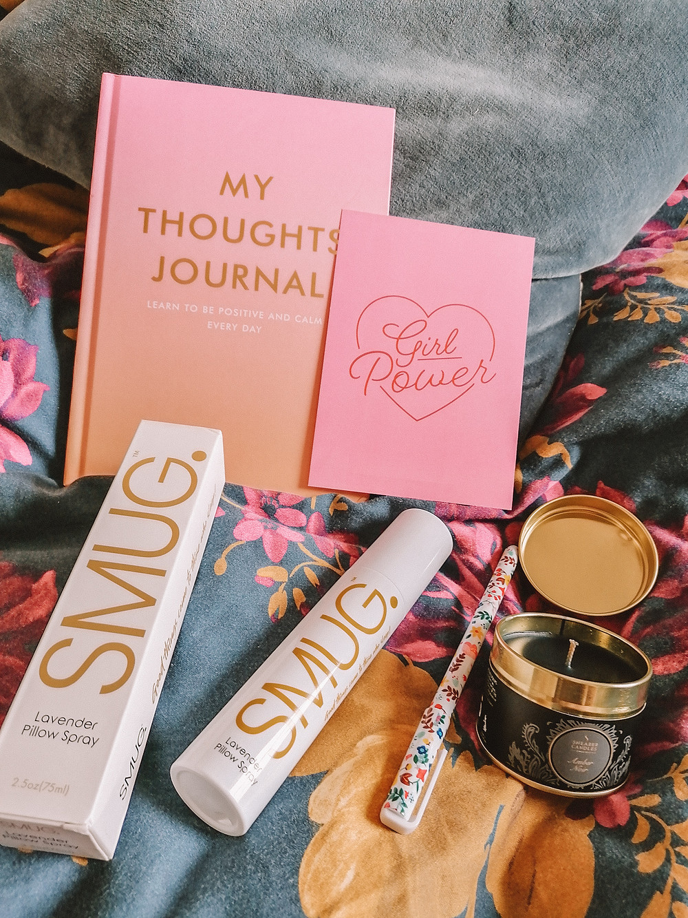 image shows smug pillow spray, a floral pen, a black candle in a pot, a pink and orange thoughts journal and a pink postcard with Girl Power written on it in red inside a red heart