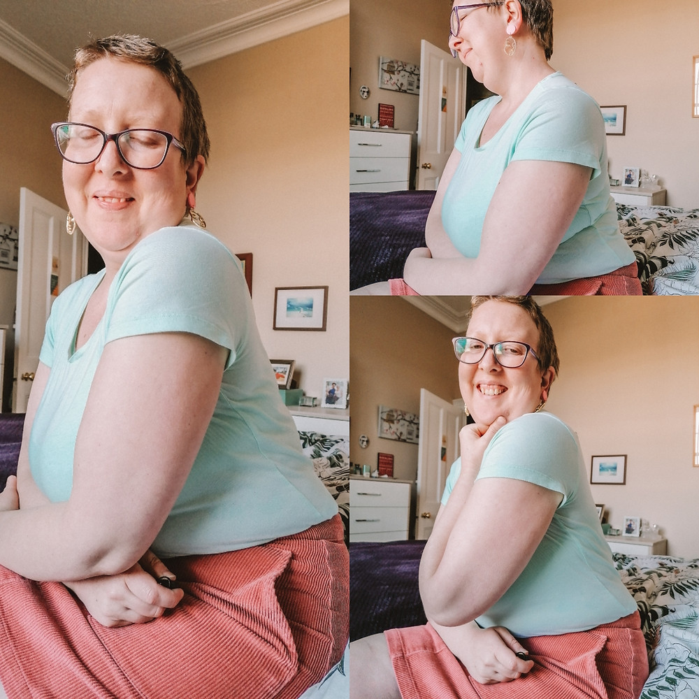 Sarah sat on the bed wearing a green t shirt, a pink cord skirt and earrings in the shape of a face