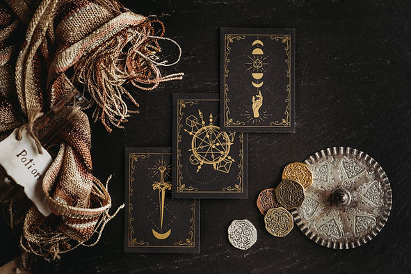 Alderdoodle spell cards on a dark wood background with a textured scarf and metal coins around them