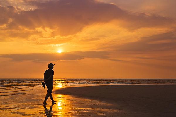 man-walking-along-the-beach-at-sunset-WEXGWC8.jpg