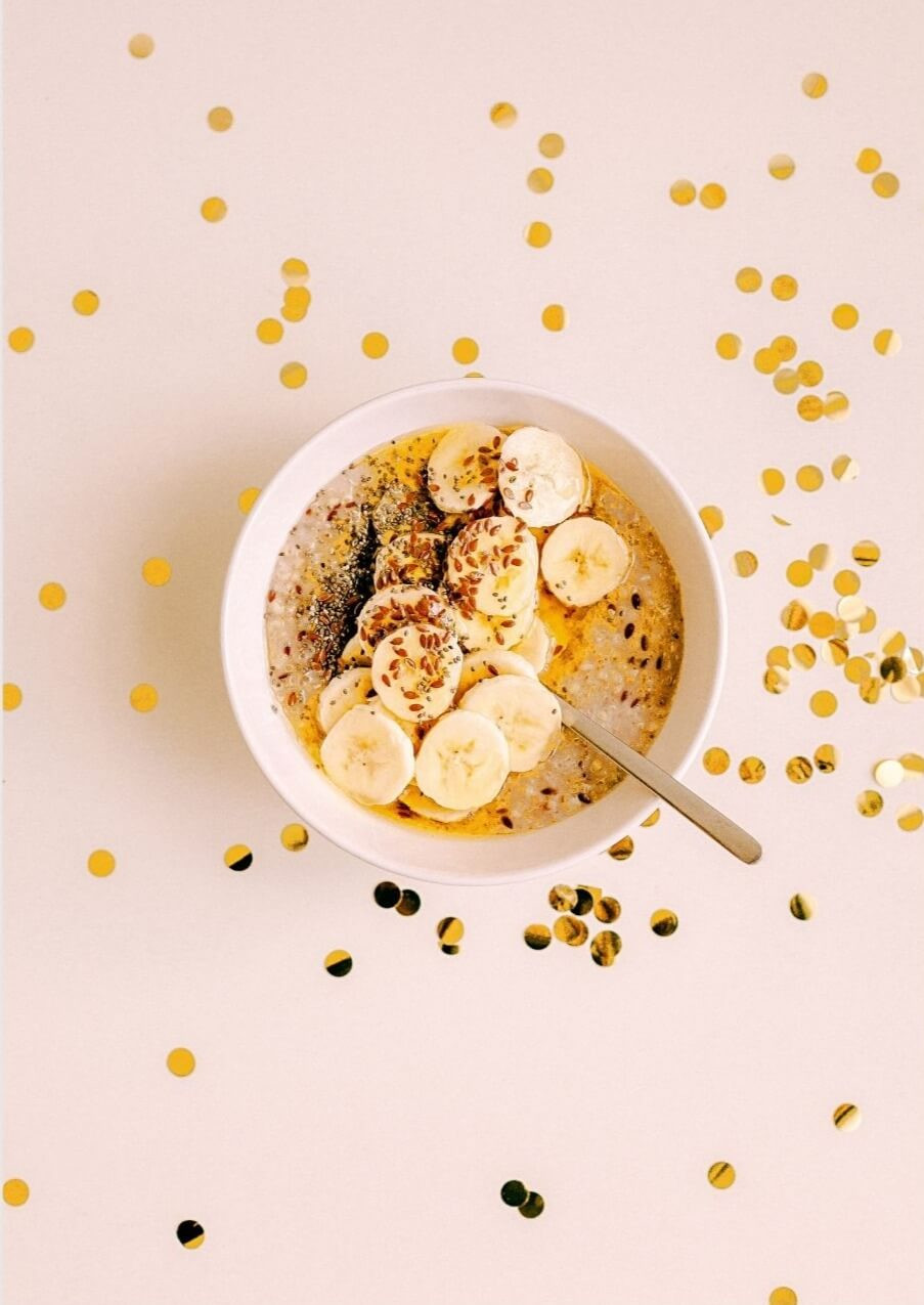 Bowl of oatmeal with bananas on pink table with gold glitter