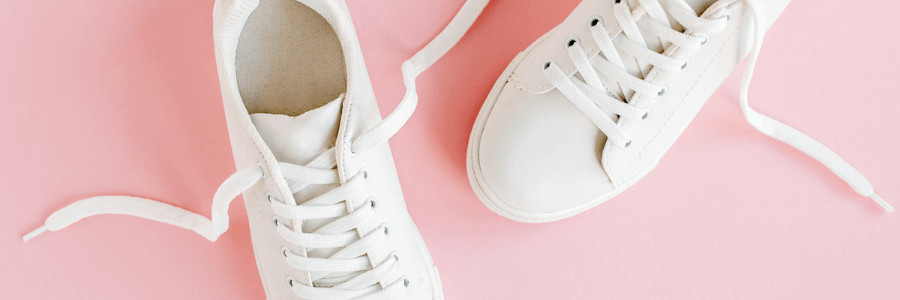 Light pink background with white sneakers