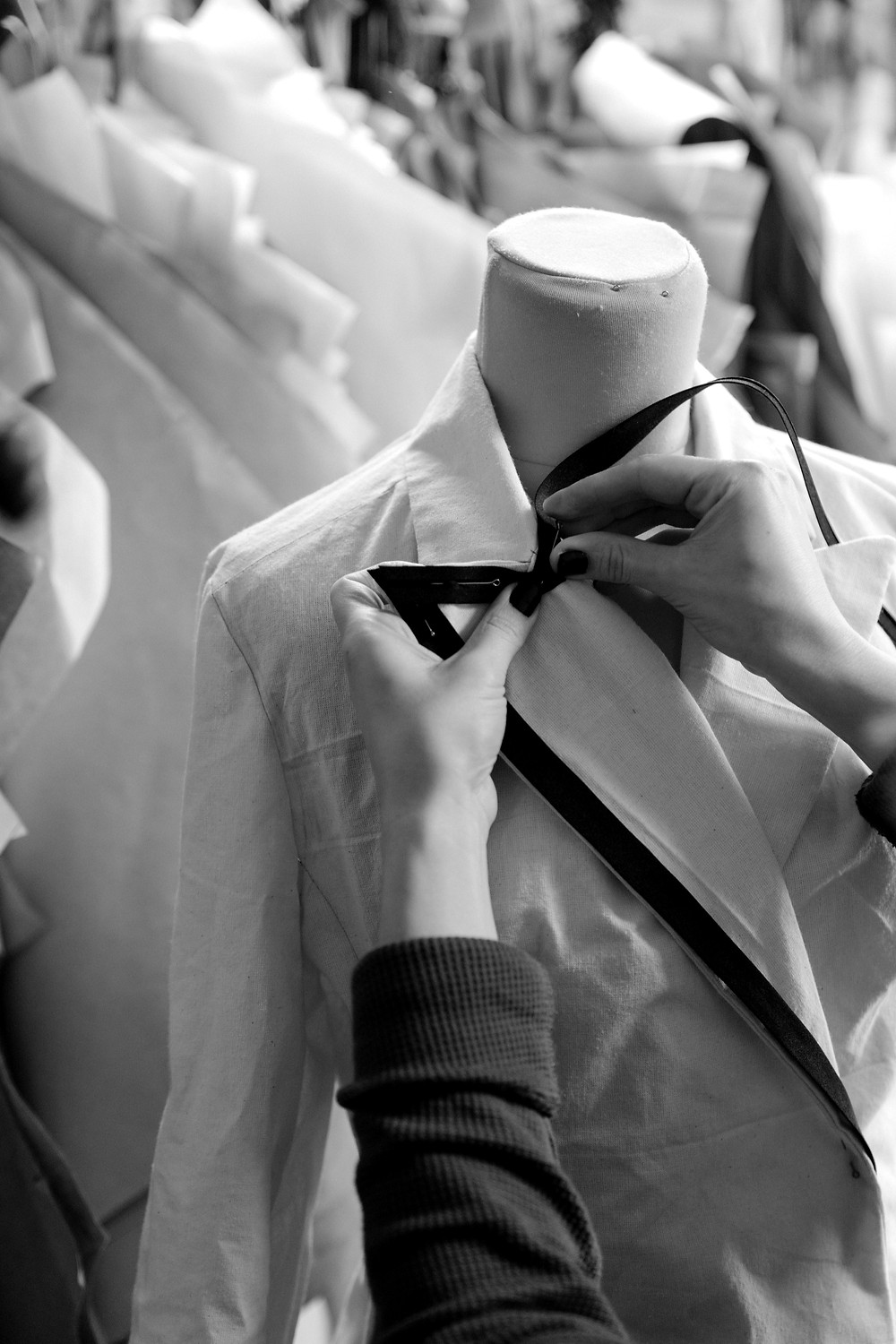A rail of clothes and a jacket being pinned on a mannequin