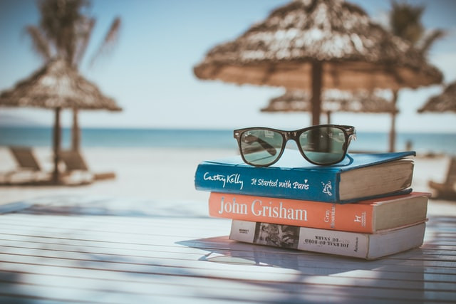 Three books, some sunglasses and a beach in the background
