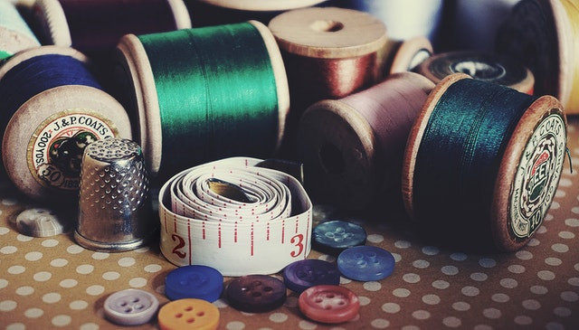 Rolls of coloured thread and buttons on a table