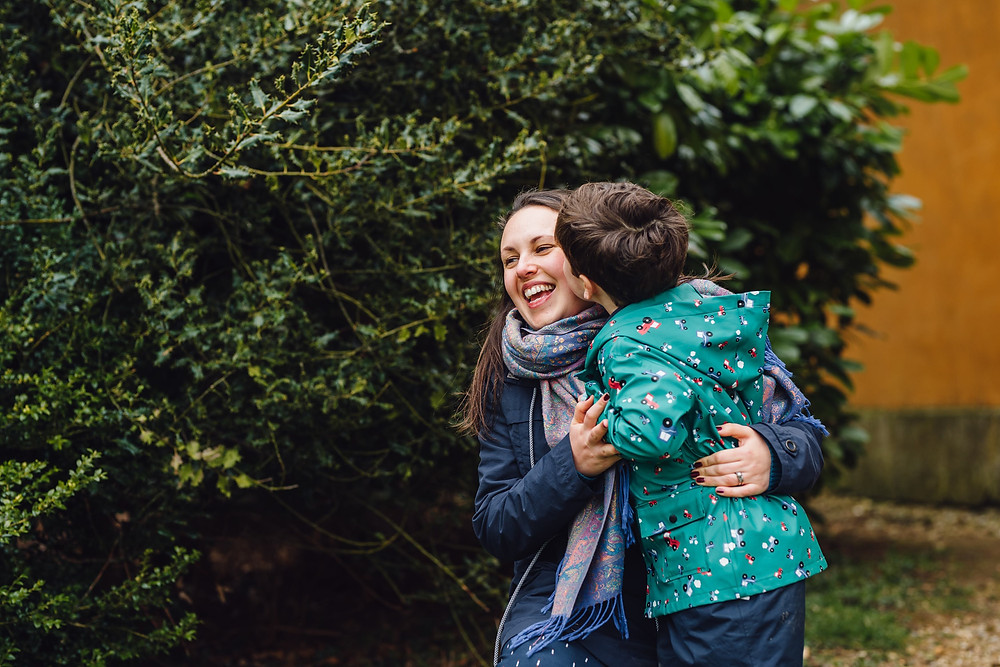 Charlie laughing with her son in front of a tree