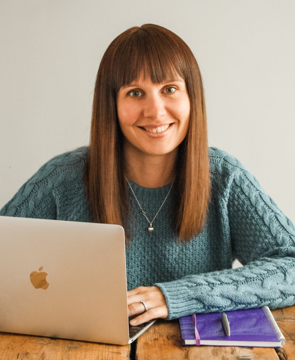 The Arts VA's Jenny sitting at a desk with a laptop