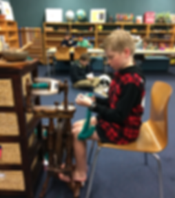 Child spins wool on a spinning whel in a Montessori classroom.