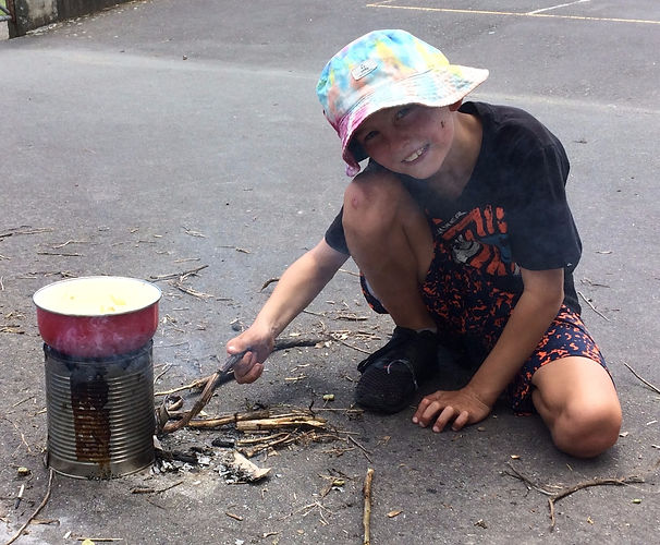 Child cooking on a hobo stove in a Montessori enviroment.