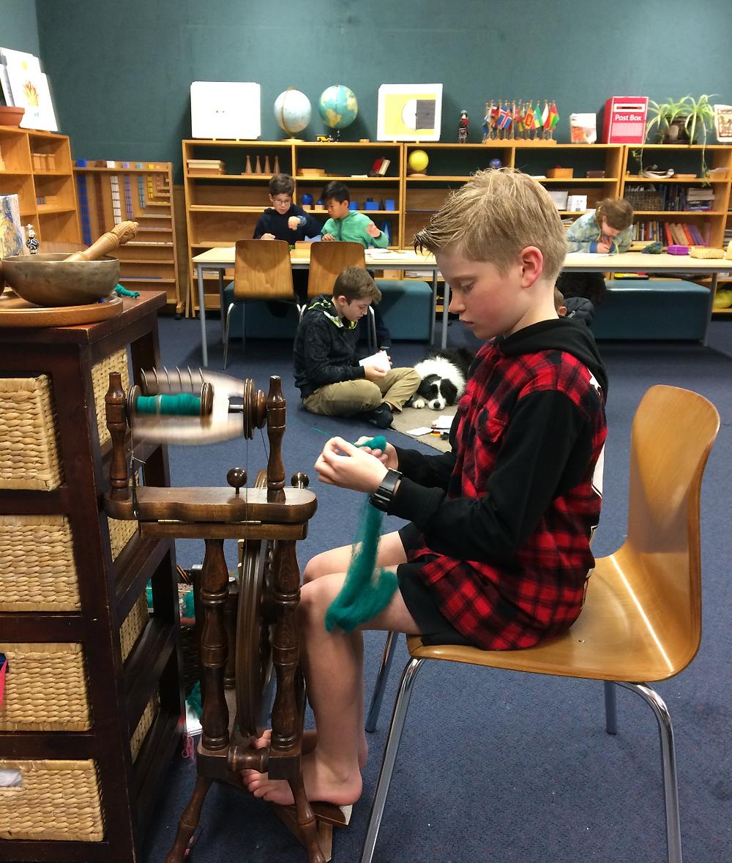 Boy spinning wool in a Montessori classroom.