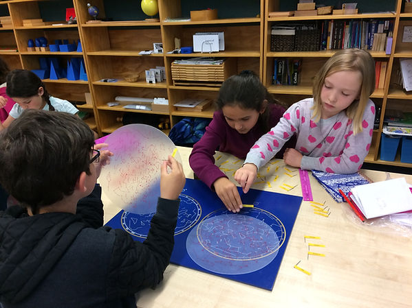 Children working on a solar system pin map in a Montessori classroom.