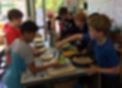 Children serving Community Lunch in a Montessori classroom.