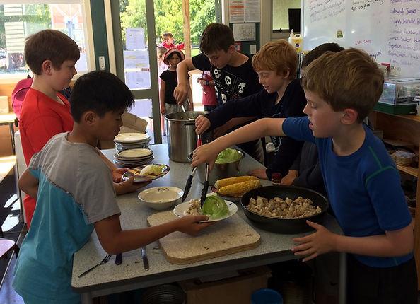 Children serving Community Lunch in a Montessori classroom.