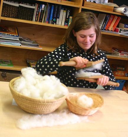 Girl carding wool in a Montessori classroom.