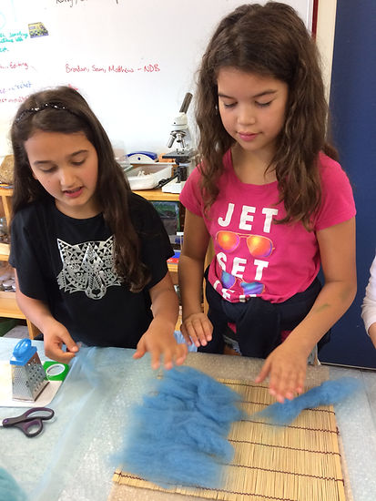 Children laying out wool for felting in a Montessori classroom.