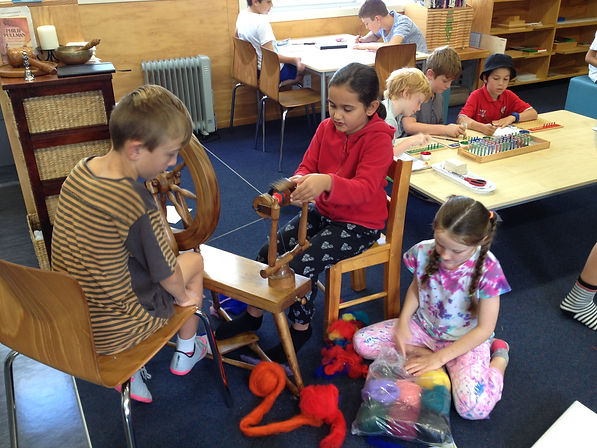 Children using a spinning wheel to spin wool in a Montessori classroom.