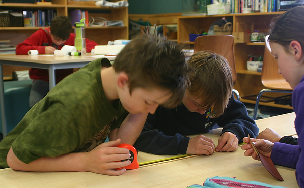 Children measuring dowel to make knitting needles in a Montessori classroom.