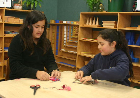 Children weaving on cardboard looms in a Montessori classroom.