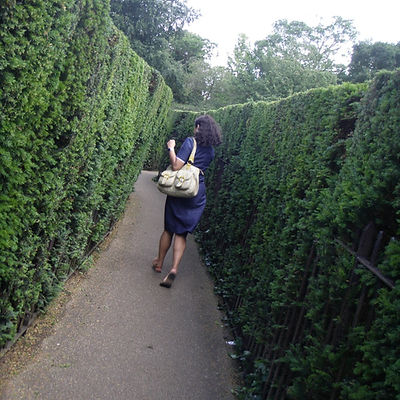 A South Asian woman in a blue dress runs away from us, between two tall green hedges.
