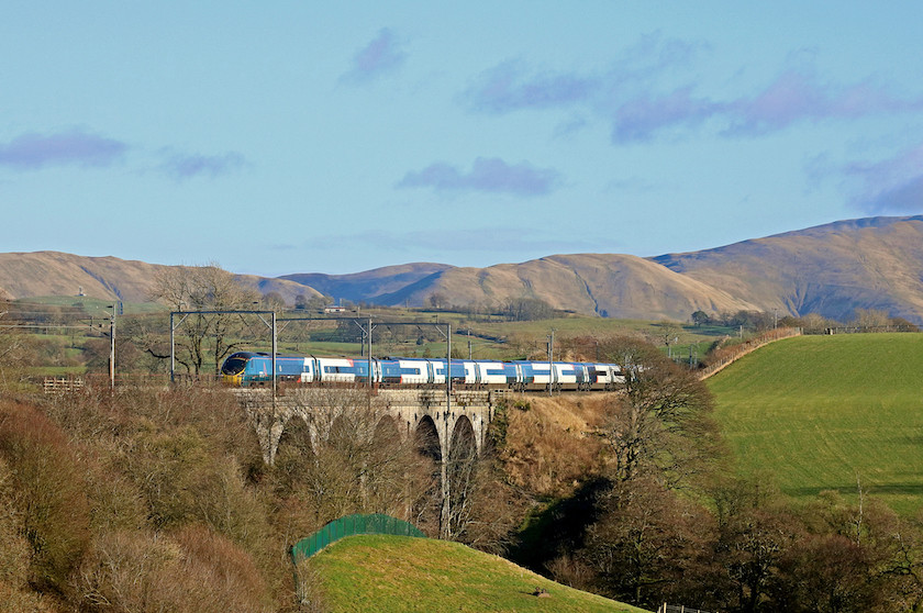 Train going over viaduct with mountain in distance