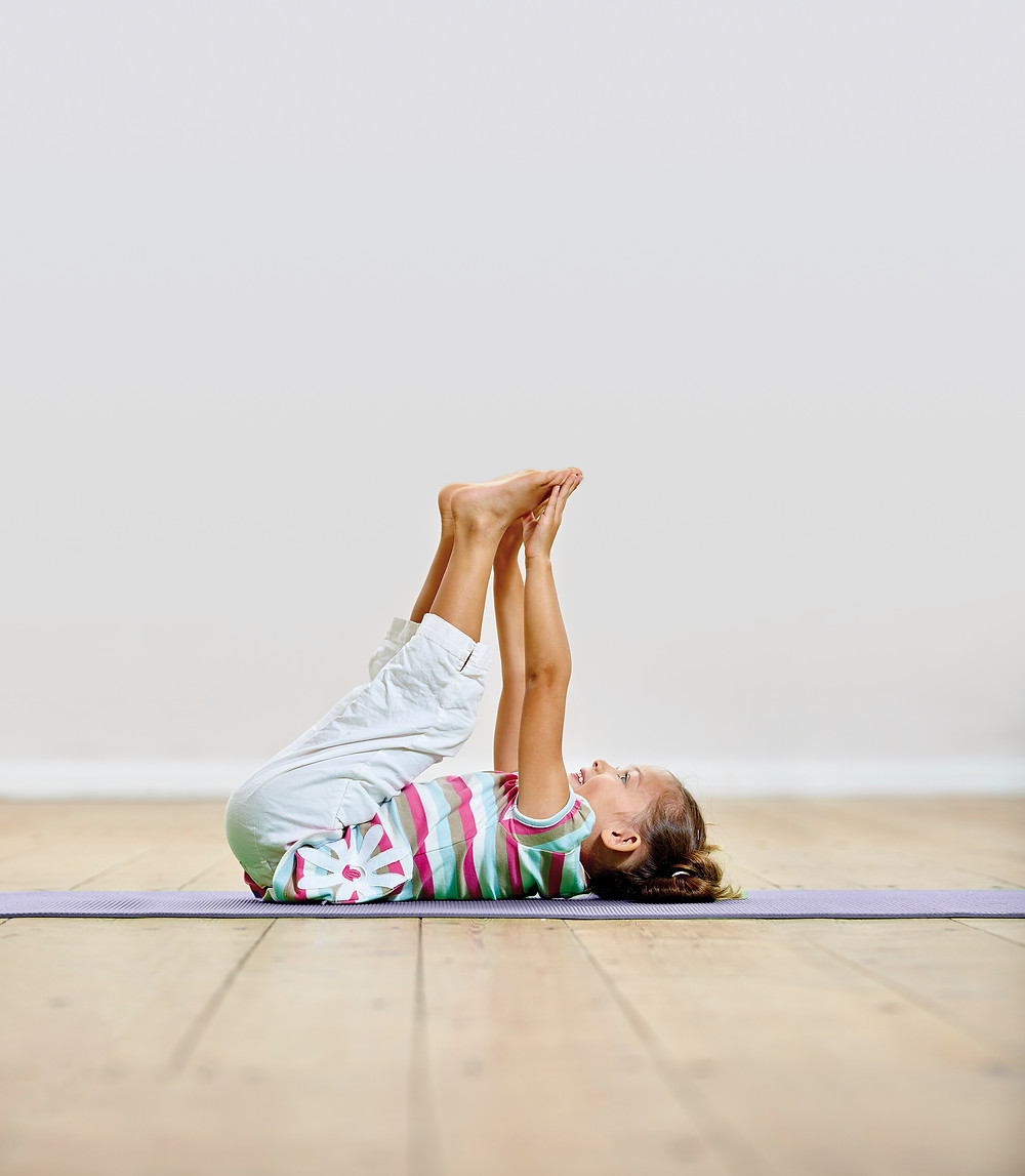 Child touching toes in yoga pose