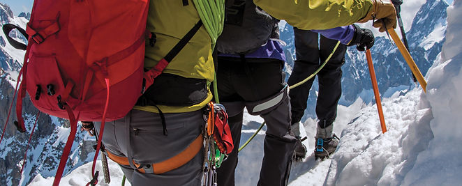 Close-up of climbers walking on snowy pa