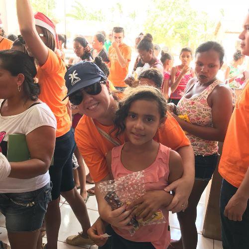 A colaboradora Cristiany Pessoa com uma das crianças beneficiadas na ação social.