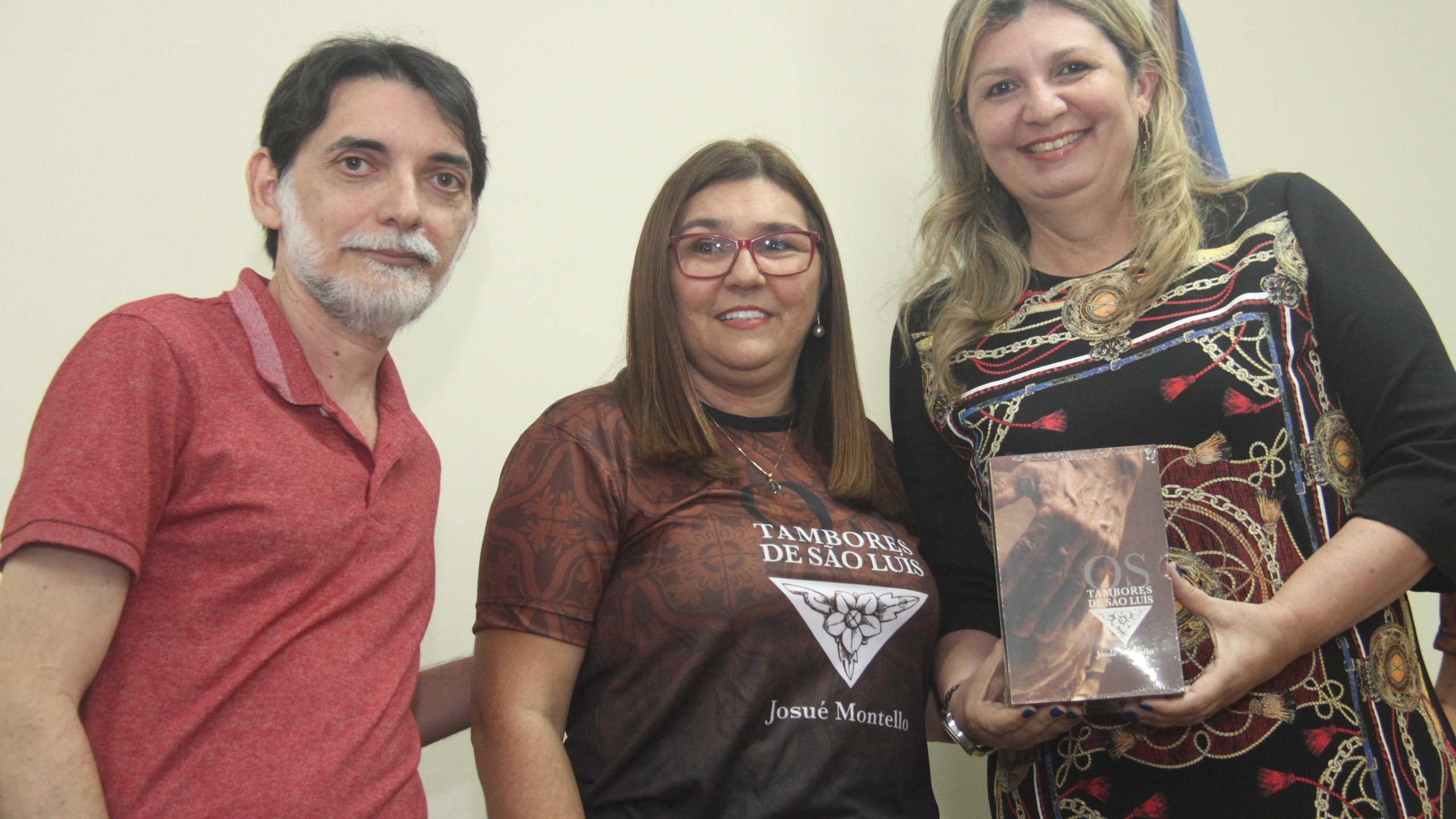 Wilson Marques e Joseane Souza fazendo a entrega dos exemplares da Biblioteca Benedito Leite à Aline Nascimento.