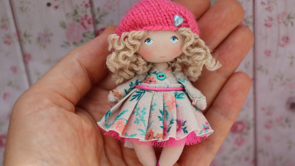 Miniature blonde rag doll in pink beret