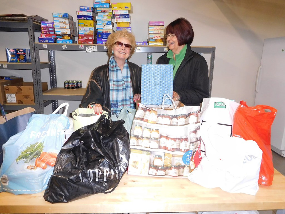 PHOTO BY JAMES PARRY On behalf of members of the Hudson Coronation Street Appreciation Society, vice-president Mireille Lemelin presents Carol Laws of Le Pont/Bridging food bank with a whole stack of non-perishable items to help local families in need in the coming weeks.