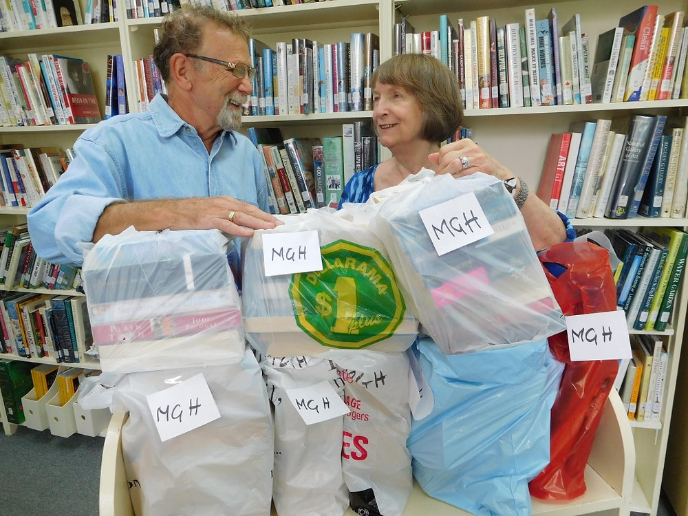 PHOTO BY JAMES PARRY En route to the Montreal General Hospital for radiation treatment, George Hine stopped by the Hudson War Memorial Library to pick up their latest donation for the Montreal General Hospital book shop from library volunteer, Donna Atwood.