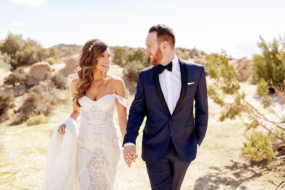 mariée et marié heureux dans le désert se tenant la main bride avec une robe de mariée et une couronne de mariée bohème