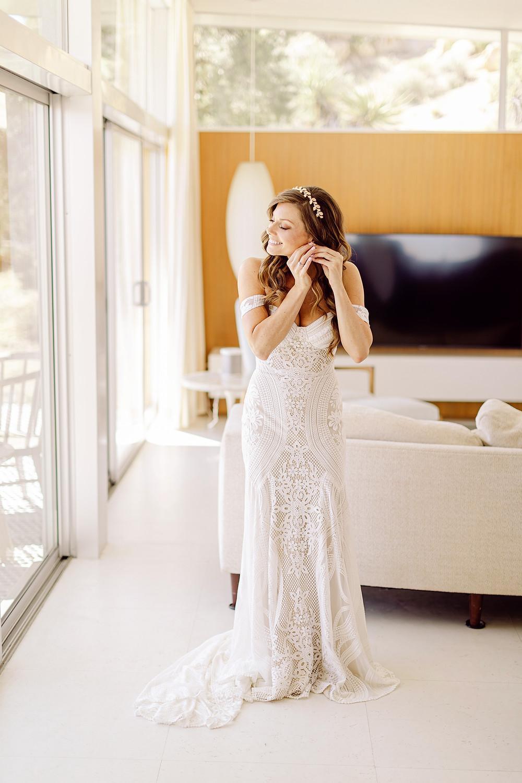 mariée mettant ses boucles d'oreilles de mariage dans son salon portant sa robe de mariée bohème et un couronne de feuille sur sa coiffure de mariée cheveux lachés