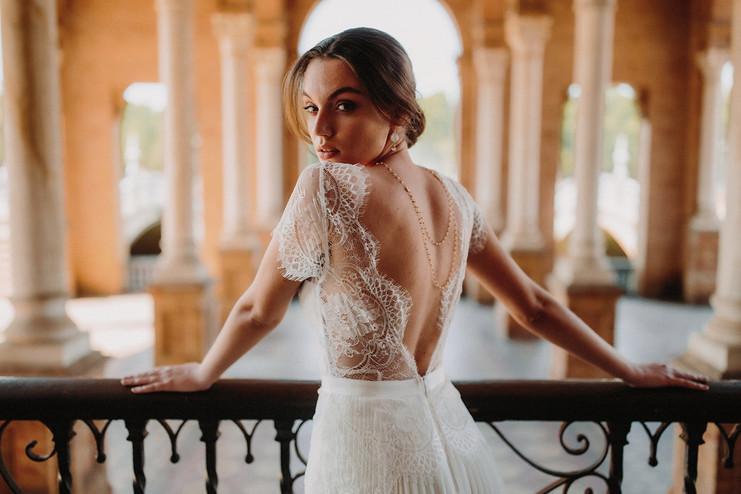 Sublime collier de dos romantique et bohème porté par une mariée sous les arcades de la plaza de espana a seville