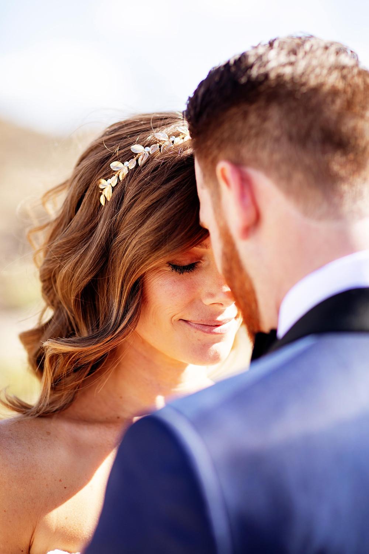 mariée fermant les yeux avec une couronne de feuilles bohème sur coiffure de mariée cheveux longs lachés et ondulés