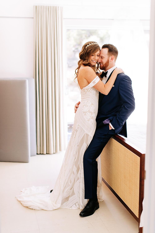 couple de mariés dans leur chambre d'hôtel enlacés avec robe de mariée et couronne de feuilles bohème