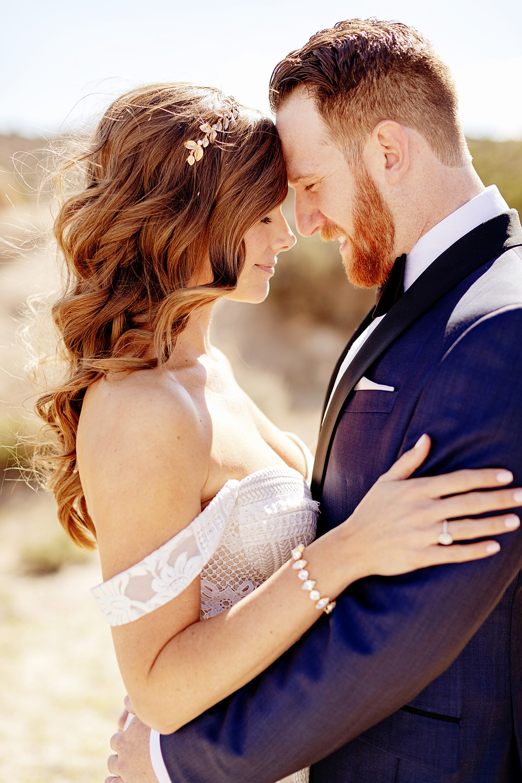 couple de mariés enlacés fermant les yeux front contre front avec couronne de mariée bohème sur cheveux laches