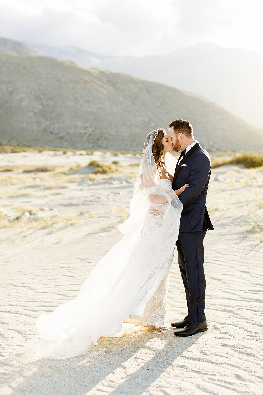 mariage dans le désert et futurs mariés qui s'embrassent, mariée avec robe de mariage et voile