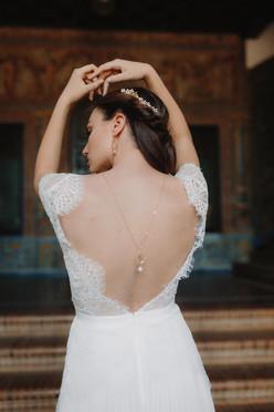 Boucles d'oreilles et collier de dos floral portés par une mariée de dos levant les bras