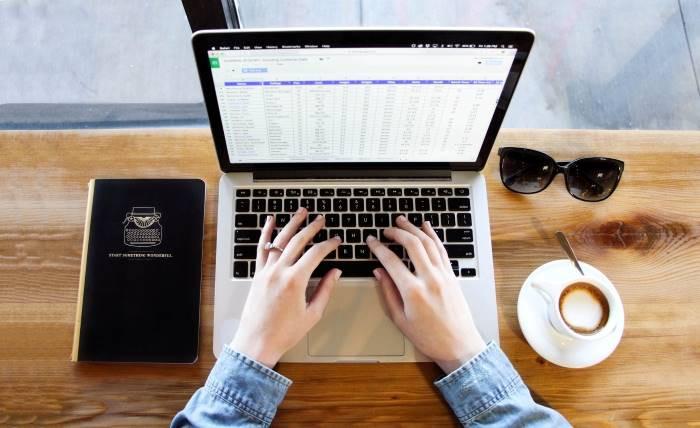 """<alt=""""notebook aberto com duas mãos sobre o teclado, no centro de uma mesa de madeira. À esquerda, um livro de capa preta e à direita um par de óculos escuros e uma xícara de café"""">"""