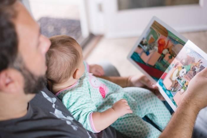 """<atl=""""homem com um bebê no colo, mostrando-lhe um livro ilustrado"""">"""