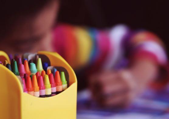 """<=""""destaque na imagem de uma caixa com lápis coloridos. Ao fundo, imagem desfocada de uma criança escrevendo"""">"""