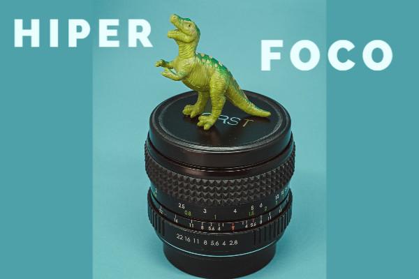 """<alt=""""dinossauro de brinquedo em cima de uma lente de máquina fotográfica. Texto na imagem diz: hiperfoco"""">"""