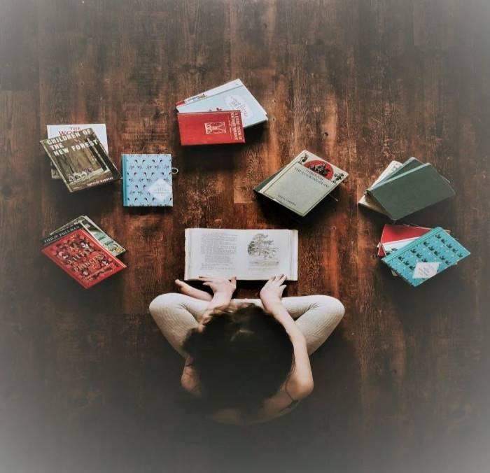 """<alt=""""menina sentada no chão com um livro aberto a sua frente e outros livros ao redor"""">"""